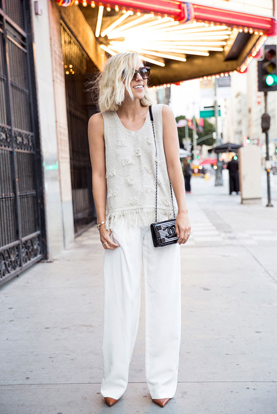 30 Chic Work Outfits to Wear this Summer: Fashion blogger 'Damsel In Dior' wearing a beige sleeveless sweater, white wide leg pants, brown heels, black round sunglasses and a black chain strap bag. Work outfits, summer work outfits, office wear, business casual, fashion, street style, womens fashion, all white outfit.