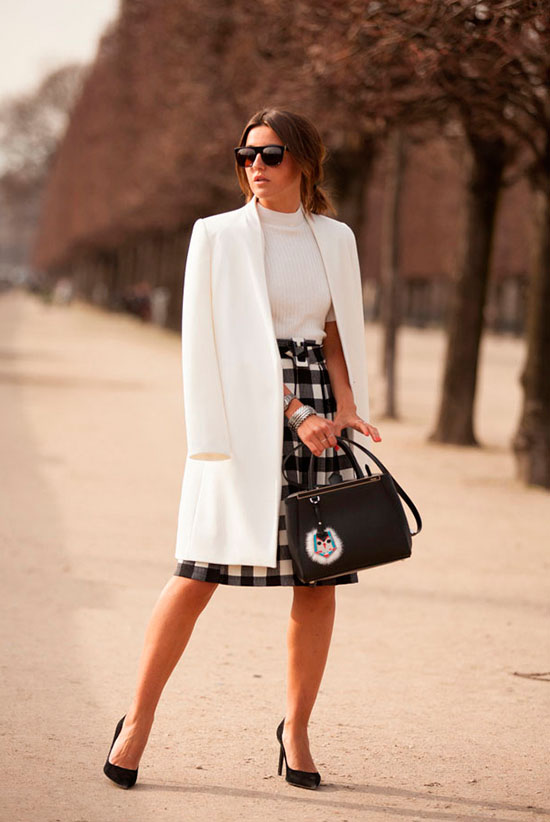 30 Chic Work Outfits to Wear this Summer: Fashion blogger 'Lovely Pepa' wearing a white long blazer, a white mock neck top, a black gingham midi skirt, black suede heels, black sunglasses and a black handbag. Work outfits, summer work outfits, office wear, business casual, fashion, street style, womens fashion, spring work outfit.