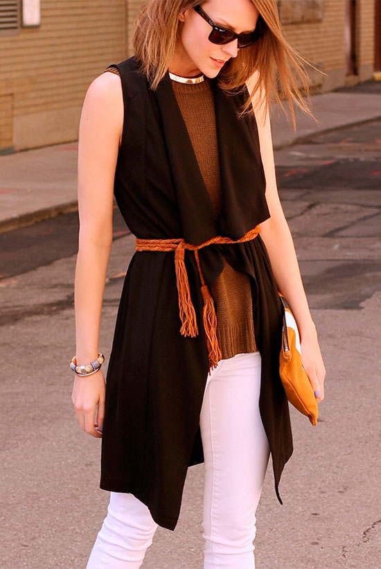 30 Chic Work Outfits to Wear this Summer: Fashion blogger 'Penny Pincher Fashion' wearing a black sleeveless duster, a brown sleeveless sweater, white skinny jeans, black sunglasses, a black tassel belt and a brown suede clutch. Work outfits, summer work outfits, office wear, business casual, fashion, street style, womens fashion.