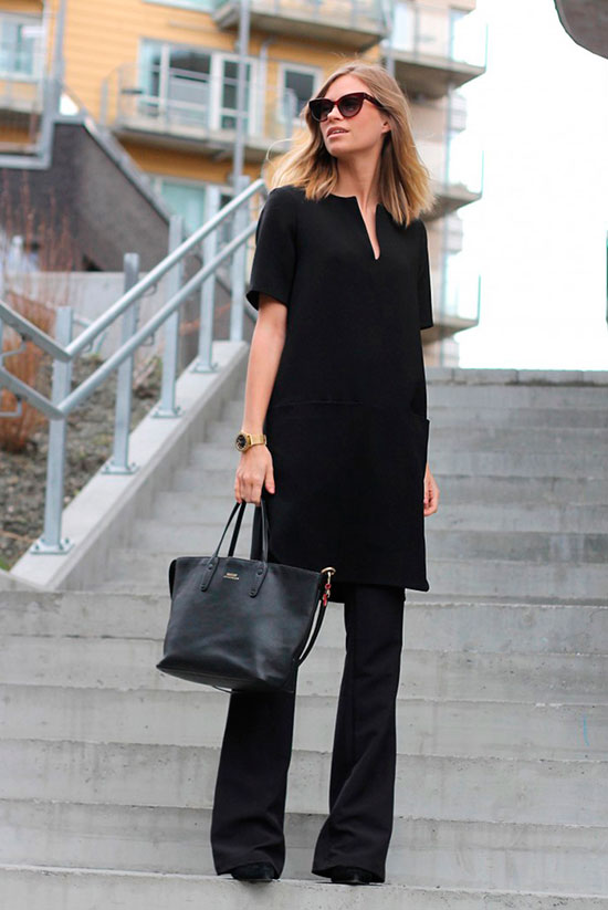 30 Chic Work Outfits to Wear this Summer: Fashion blogger 'The Fashion Eaters' wearing a black short sleeve shift dress over black flare jeans, black suede heels, black sunglasses and a black handbag. Work outfits, summer work outfits, office wear, business casual, fashion, street style, womens fashion, spring work outfits.