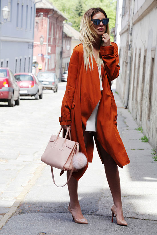 30 Chic Work Outfits to Wear this Summer: Fashion blogger 'Zorannah' wearing an orange trench coat, a white midi dress, nude heels, black sunglasses and a beige bag. Work outfits, summer work outfits, office wear, business casual, fashion, street style, womens fashion, spring work outfits.