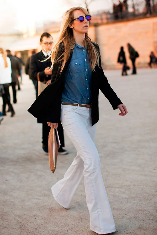 30 Chic Work Outfits to Wear this Summer: Woman wearing a black blazer, a denim shirt, white flare jeans, brown heels, clubmaster sunglasses and a beige clutch. Work outfits, summer work outfits, office wear, business casual, fashion, street style, womens fashion, spring work outfits.