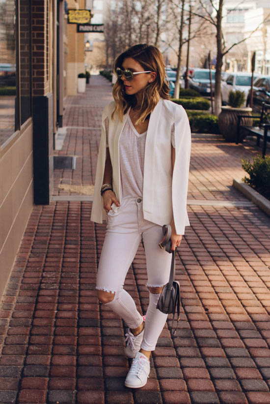 Street Style - The Top Blogger Looks Of The Week: Fashion Blogger 'Cella Jane' wearing a white cape blazer, a white v-neck t-shirt, distressed white skinny jeans, white sneakers, mirror sunglasses and a light grey shoulder bag