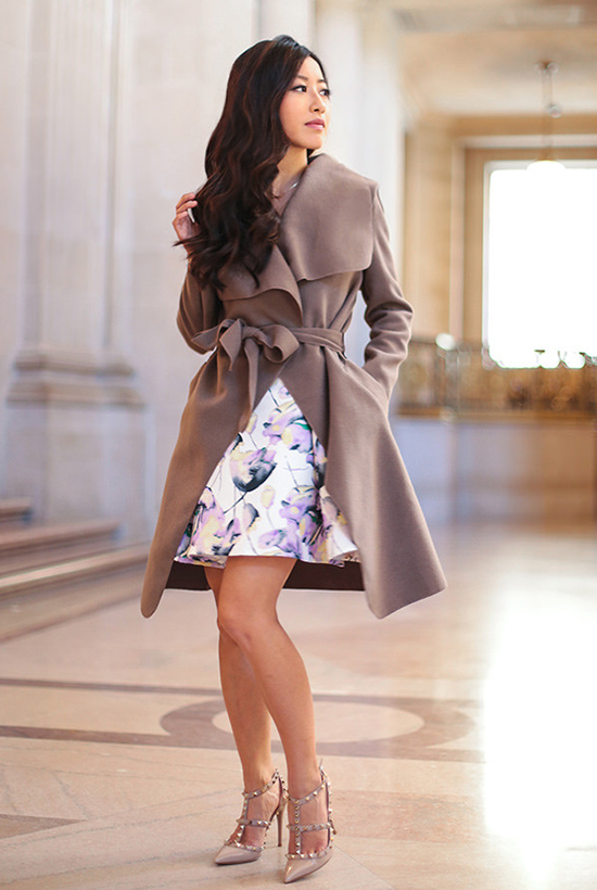 18 Lovely Valentine's Day Outfit Ideas: Blogger 'Extra Petite' wearing a camel belted coat with a white floral print fit & flare dress and nude heels