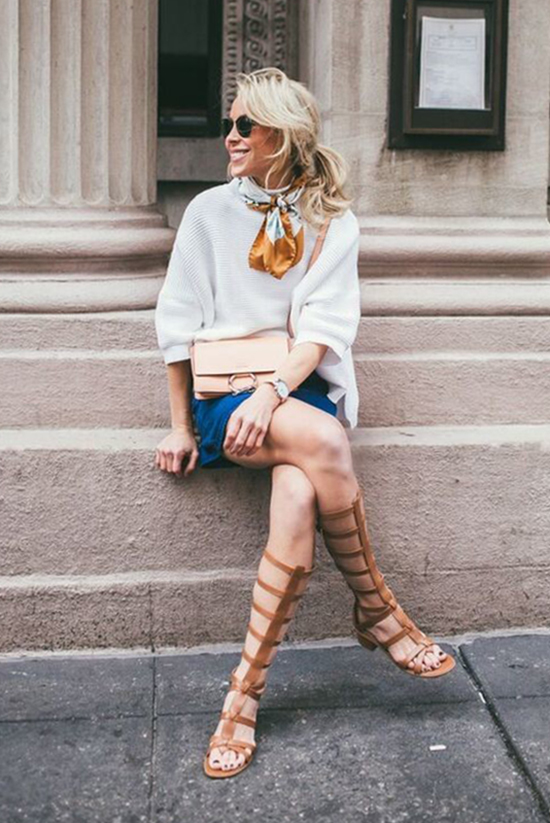 Street Style - The Top Blogger Looks Of The Week: Fashion Blogger 'Happily Grey' wearing a white boxy ribbed sweater, a button-front A-line mini skirt, brown gladiator sandals, a gold and white neckerchief, black sunglasses and a nude shoulder bag