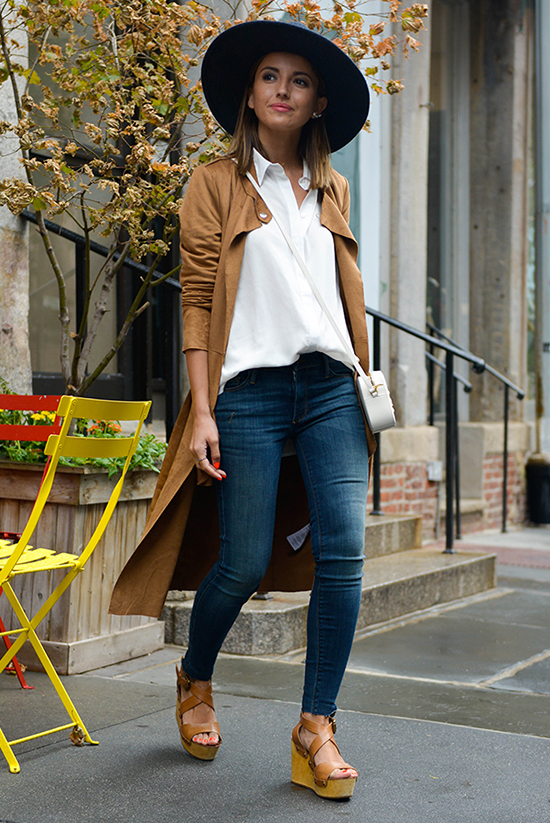 Street Style - The Top Blogger Looks Of The Week: Fashion Blogger 'Lovely Pepa' wearing a navy wide brim hat, a brown suedette duster coat, a white shirt, skinny jeans, brown platform wedges and a whit shoulder bag