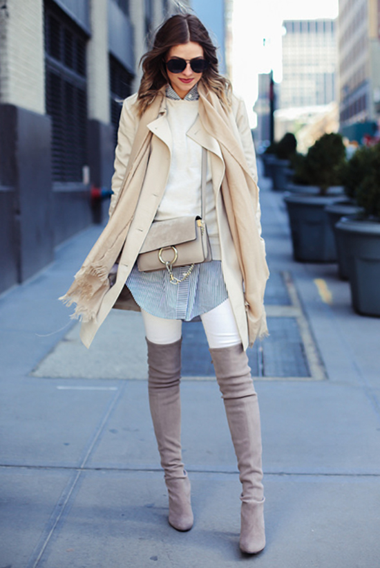 Street Style - The Top Blogger Looks Of The Week: Fashion Blogger 'Navy Grace' wearing a beige trench coat, a beige scarf, a white sweater, a blue and white striped long line shirt, white skinny jeans, light grey suede over the shoulder boots, black sunglasses and a light grey shoulder bag