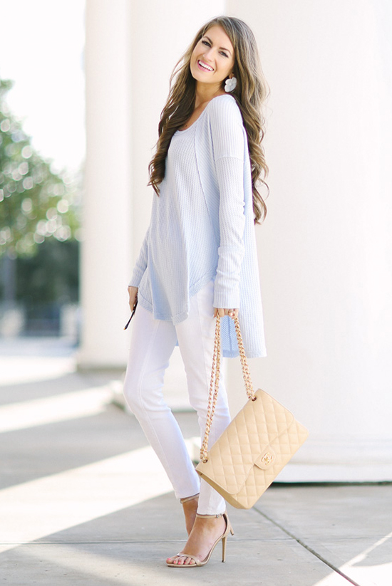 Street Style - The Top Blogger Looks Of The Week: Fashion Blogger 'Southern Curls & Pearls' wearing a baby blue sweater tunic, white skinny jeans, nude ankle strap heeled sandals and a nude quilted shoulder bag
