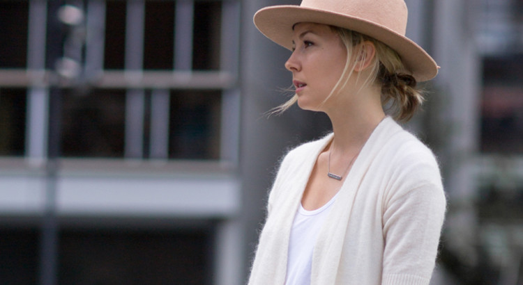 Street Style - Subtle Sophistication: Fashion Blogger 'The Rue Collective' wearing a cream long cardigan, a white t-shirt, black skinny jeans, white sneakers, a nude fedora and a light brown bucket bag