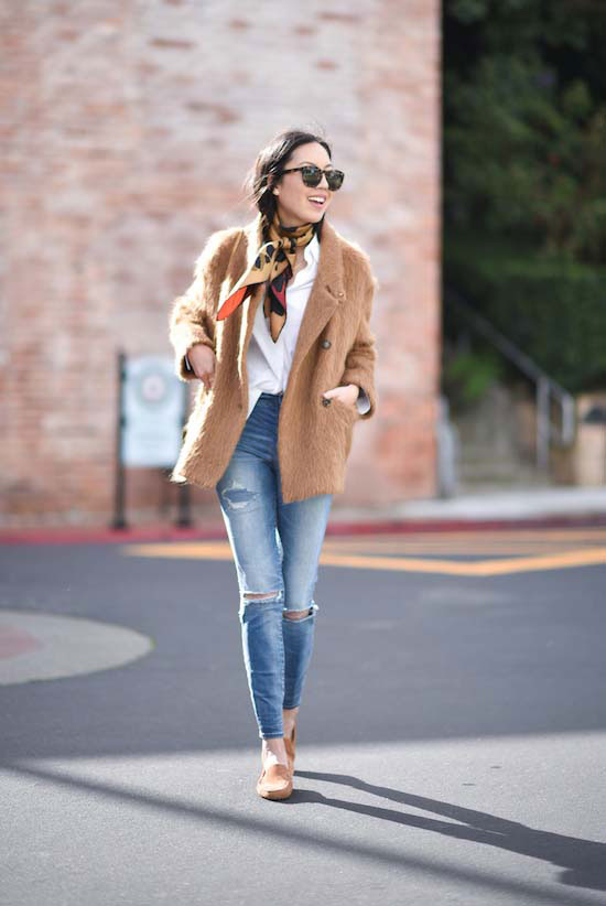 Street Style - The Top Blogger Looks Of The Week: Fashion blogger '9 to 5 Chic' wearing a camel boxy coat, a white shirt, a gold silk scarf, skinny jeans, light brown suede loafers and brown sunglasses