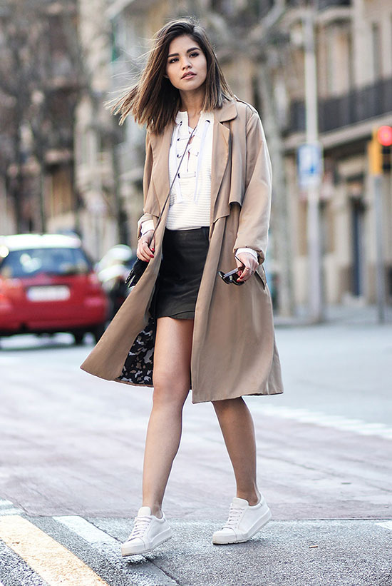street style - The Top Blogger Looks Of The Week: Fashion Blogger 'Fake Leather' wearing a beige trench coat, a white lace up blouse, a black leather mini skirt, white sneakers and a black shoulder bag - spring outfit - fall outfit