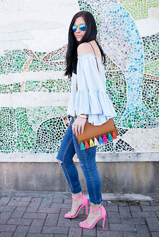 street style - The Top Blogger Looks Of The Week: Fashion Blogger 'Gal About Town' wearing a light blue off shoulder peplum top, skinny jeans, pink ankle strap heeled sandals, aviator sunglasses and a brown tassel shoulder bag - summer outfit