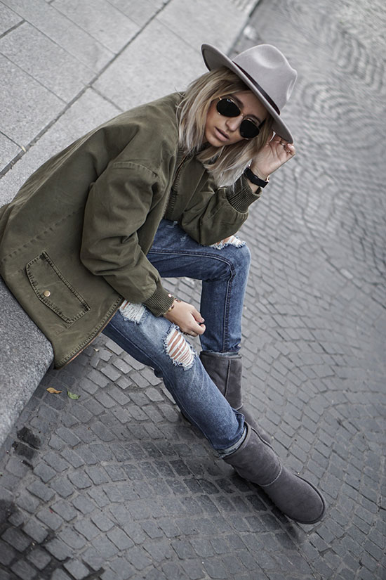 Street Style - The Top Blogger Looks Of The Week: Fashion blogger 'Noholita' wearing a grey fedora, an olive utility jacket, distressed skinny jeans, grey suede lined ankle boots, a grey patterned scarf and a white t-shirt