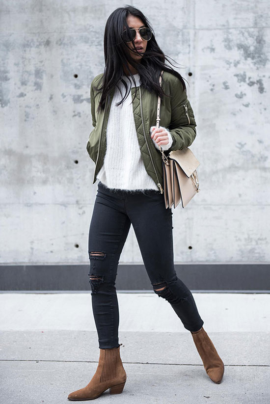 bomber jacket - The Bomber Is Fashion's Favorite Spring Jacket: Fashion blogger 'Not Your Standard' wearing a military green bomber jacket, a white fuzzy sweater, black distressed skinny jeans, brown western booties, aviator sunglasses and a beige shoulder bag. fall outfits, winter outfits, spring outfits, comfy outfits, bomber jacket outfits