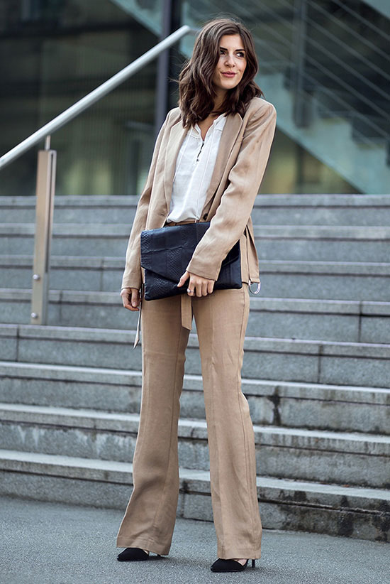 spring work outfits - 30 Spring Work Outfits To Try Right Now: Fashion Blogger 'Simple Et Chic' wearing a light brown blazer, a white v-neck blouse, light brown flare suit pants, black pointy toe heels and a black envelope clutch