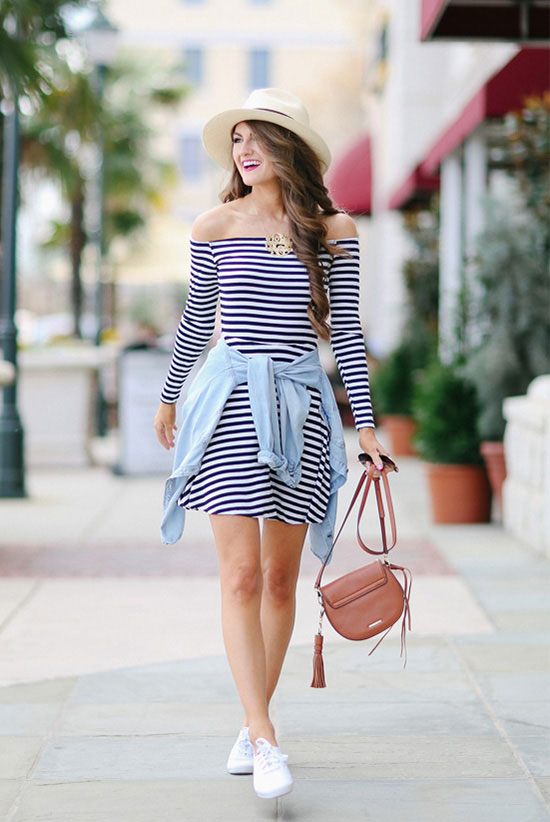 street style - The Top Blogger Looks Of The Week: Fashion blogger 'Southern Curls & Pearls' wearing a straw fedora, a black and white off shoulder long sleeve bodycon dress, white sneakers, a chambray shirt and a brown saddle bag. Summer outfits, beach outfits, comfy outfits, getaway outfits, vacation outfits, travel outfits, casual outfits