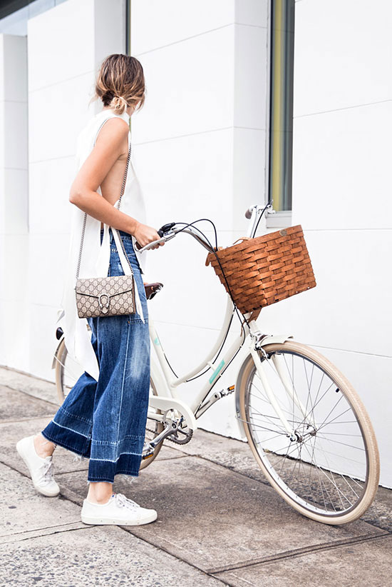 Street Style - The Top Blogger Looks Of The Week: Fashion blogger 'The Chronicles of Her' wearing a white sleeveless side slit knit tunic, denim culottes, white sneakers and a beige logo shoulder bag