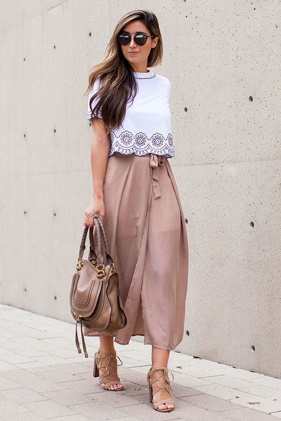 street style - The Top Blogger Looks Of The Week: Fashion Blogger 'The Darling Detail' is wearing a white short sleeve embroidered crop top, a light pink belted wrap midi skirt, nude lace up block heel sandals, black sunglasses and a brown handbag - spring outfit - summer outfit - beach outfit - getaway outfit
