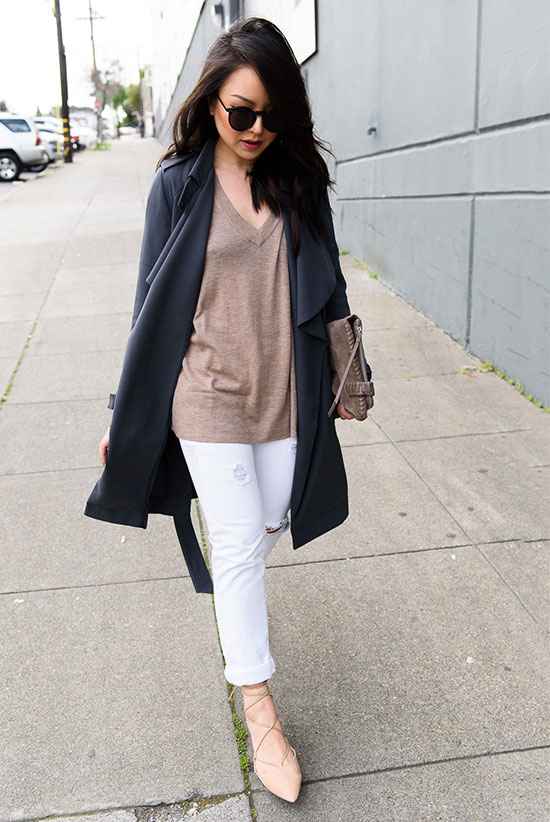 Street Style - The Top Blogger Looks Of The Week: Fashion blogger 'The Fancy Pants Report' wearing a dark grey trench coat, a taupe v-neck light sweater, white distressed skinny jeans, nude lace-up flats, black sunglasses and a taupe suede clutch