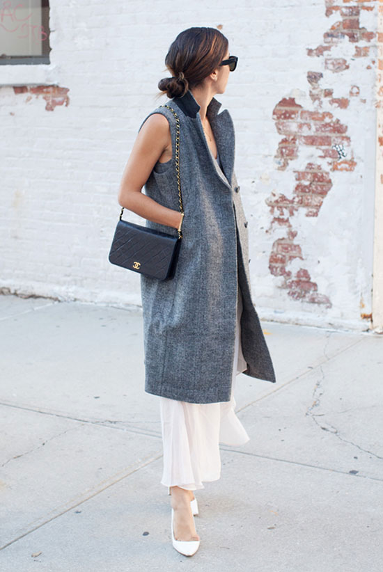 spring work outfits - 30 Spring Work Outfits To Try Right Now: Fashion Blogger 'This Time Tomorrow' wearing a grey long sleeveless coat, a light grey cami top, a white pleated chiffon midi skirt, black sunglasses, a black shoulder bag and white pointy toe heels.