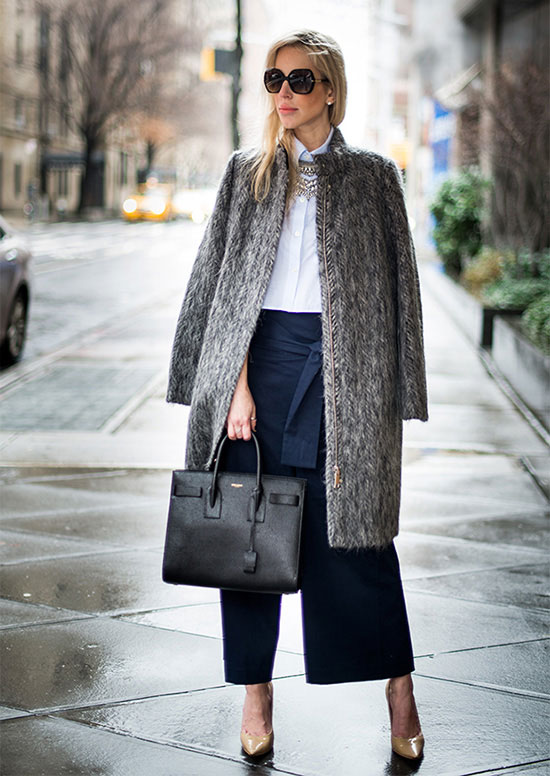 Street Style - The Top Blogger Looks Of The Week: Fashion blogger 'Yael Steren' wearing a grey furry coat, a white shirt, a statement necklace, denim culottes, nude pointy toe heels, a black satchel and black sunglasses