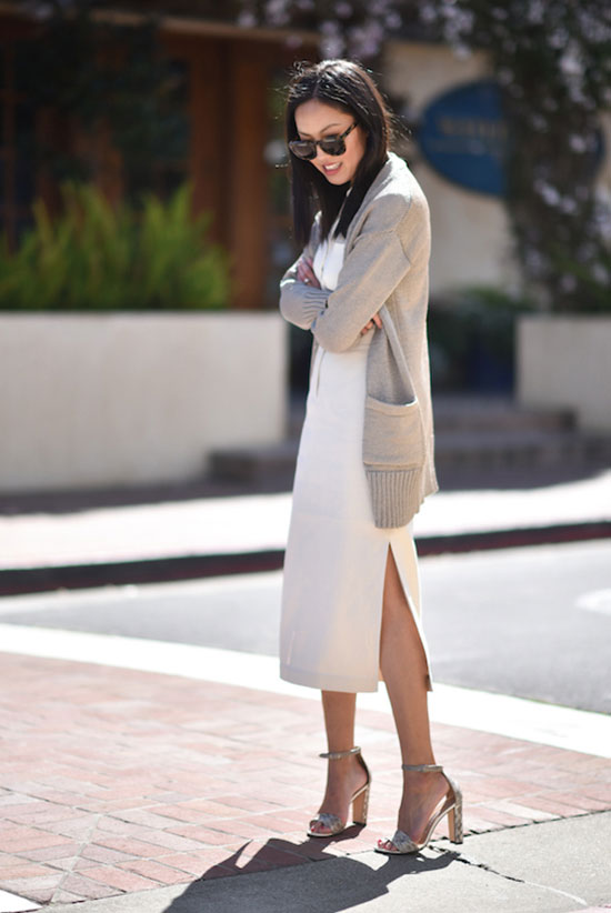Street Style - The Top Blogger Looks Of The Week: Fashion blogger '9 to 5 Chic' wearing a beige chunky cardigan, a white boxy midi dress, metallic ankle strap heeled sandals and black sunglasses. Spring outfit, summer outfit, casual outfit, street chic style, work outfit, office outfit, casual friday outfit.