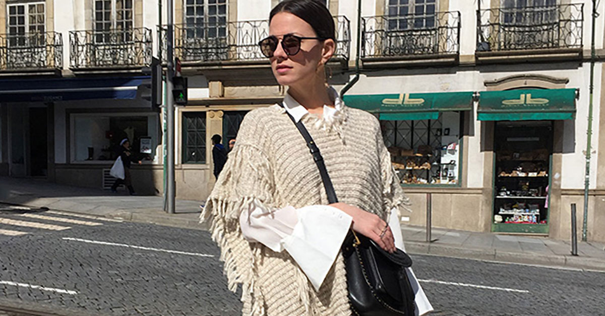 Fall Outfit - A Chic Take On All-Over Fringe: Fashion Blogger 'Fashion Vibe' wearing a beige fringe poncho, a white boyfriend shirt, fringe crop jeans, black booties, black sunglasses and a black tassel shoulder bag. Fall outfit, winter outfit, casual outfit, ootd, boho chic outfit, boho outfit, comfy outfit, street style, street chic style.