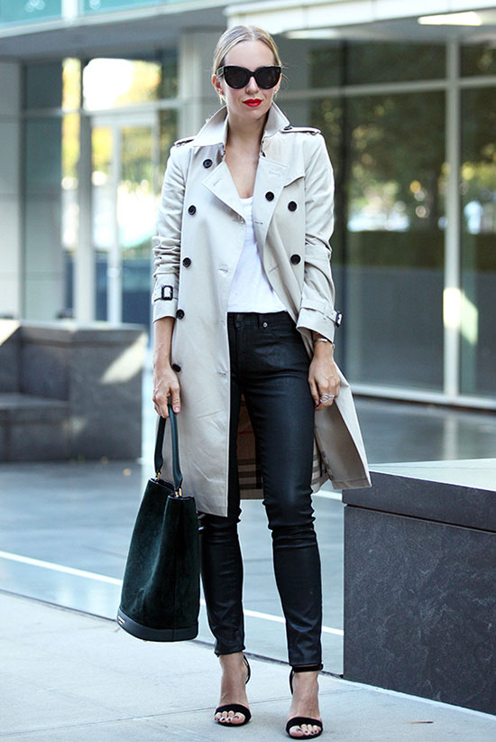 20 Ways To Style Your Favorite Trench Coat: Fashion Blogger 'Brooklyn Blonde' wearing a beige trench coat, a white v-neck t-shirt, black leather pants, black heeled sandals, black sunglasses and a black tote bag. Trench coat outfit, spring outfit, fall outfit, street chic style, casual outfit, night out outfit.