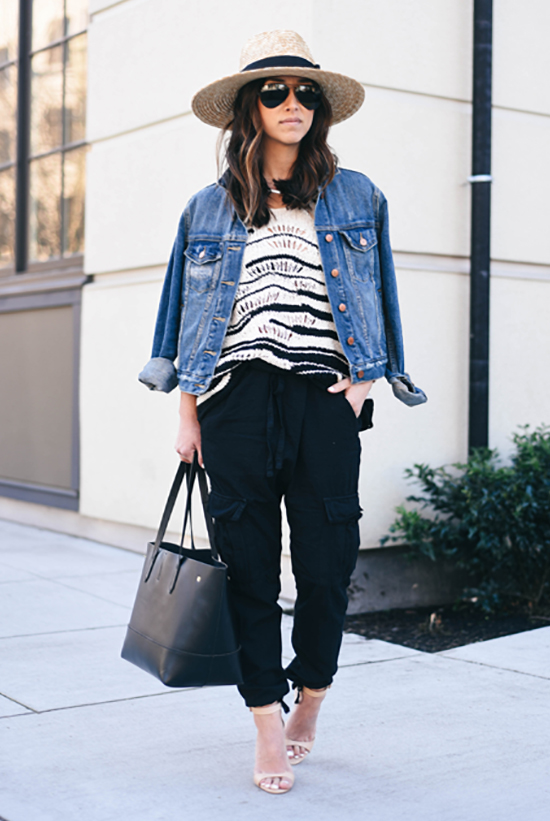 Street Style - The Top Blogger Looks Of The Week: Fashion blogger 'Crystalin Marie' wearing a straw fedora, a black and white knit top, black joggers, nude heeled sandals, a denim jacket, aviator sunglasses and a black tote bag. Summer outfit, casual outfit, street chic style.