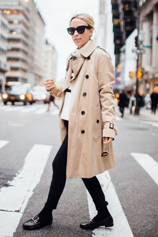 20 Ways To Style Your Favorite Trench Coat: Fashion Blogger 'Damsel In Dior' wearing a beige trench coat, a stripe sweater, black skinny jeans, black tights, black loafers and black sunglasses. Trench coat outfit, fall outfit, winter outfit, work outfit, office outfit, comfy outfit, tomboy outfit, street style, street chic style.