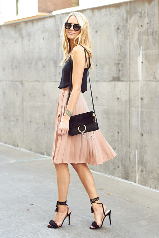 Street Style - The Top Blogger Looks Of The Week: Fashion blogger 'Fashion Jackson' wearing a black cami top, a pale pink pleated skirt, black lace up sandals, black sunglasses and a black shoulder bag. Summer outfit, party outfit, night out outfit, street chic style.