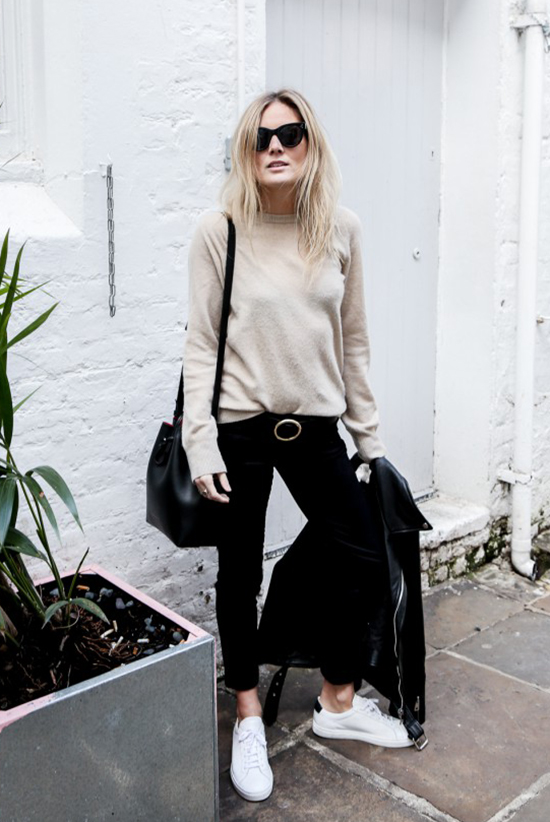Street Style - The Top Blogger Looks Of The Week: Fashion blogger 'Fashion Me Now' wearing a beige sweater, black ankle pants, a black buckle belt, white sneakers, a black leather jacket, black sunglasses and a black shoulder bag. Spring outfit, fall outfit, comfy outfit, sneakers outfit, casual outfit, athleisure, easy outfit.