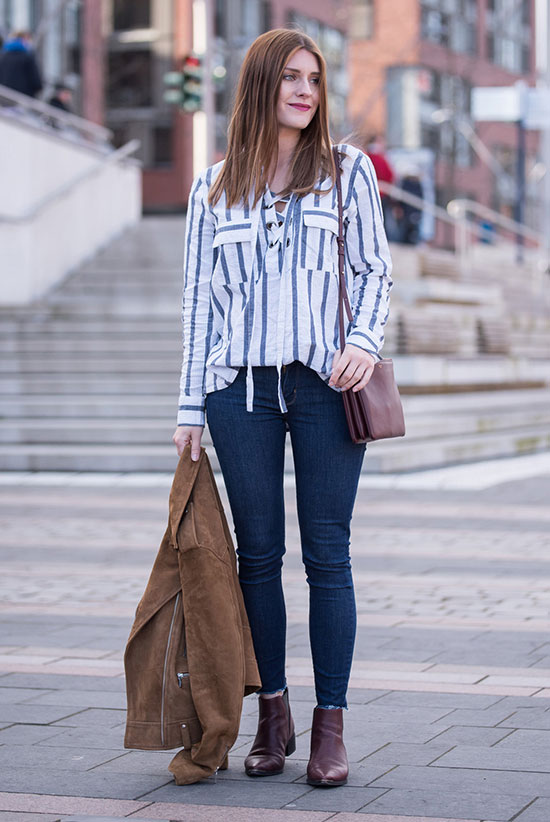 Street Style - The Top Blogger Looks Of The Week: Fashion blogger 'Hoard Of Trends' wearing a brown suede jacket, a blue stripe lace-up blouse, skinny jeans, burgundy booties and a burgundy shoulder bag. Casual outfit, spring outfit, fall outfit, boho chic outfit, boho outfit, comfy outfit.