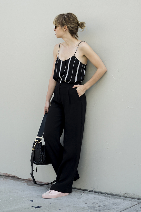 Street Style - The Top Blogger Looks Of The Week: Fashion blogger 'Just Another' wearing a black stripe cami top, black wide leg pants, pale pink sneakers, round sunglasses and a black shoulder bag. Casual outfit, comfy outfit, athleisure, summer outfit.