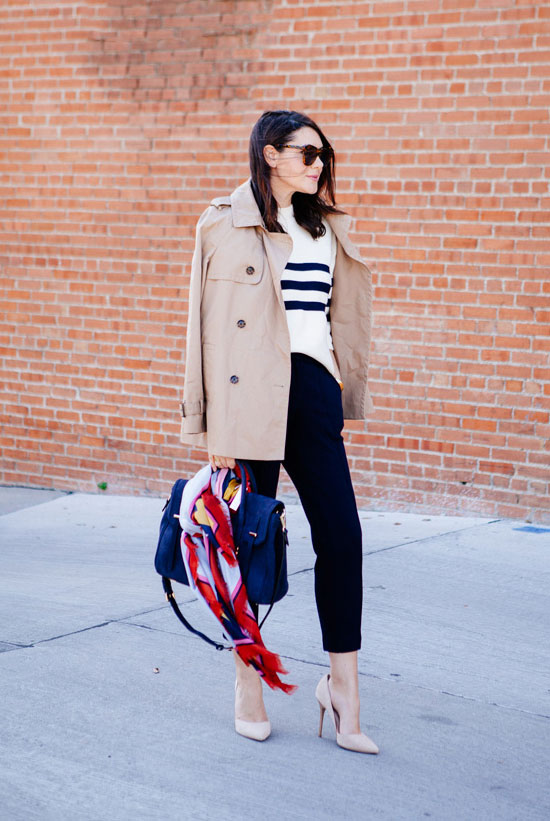 20 Ways To Style Your Favorite Trench Coat: Fashion Blogger 'Kendi Every Day' wearing a beige trench coat, a stripe sweater, black ankle pants, nude heels, brown sunglasses, a navy handbag and a colorful scarf. Trench coat outfit, fall outfit, work outfit, office outfit, street chic style, casual outfit.