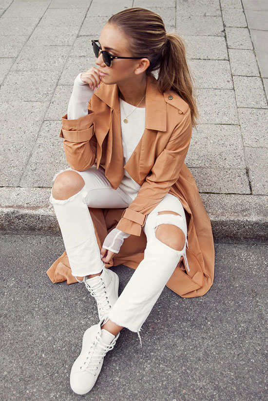20 Ways To Style Your Favorite Trench Coat: Fashion Blogger 'Lisa Olsson' wearing a brown trench coat, a white long sleeve t-shirt, white distressed skinny jeans, white high top sneakers and black clubmaster sunglasses. Trench coat outfit, spring outfit, fall outfit, comfy outfit, casual outfit, sneakers outfit, athleisure outfit, street style.
