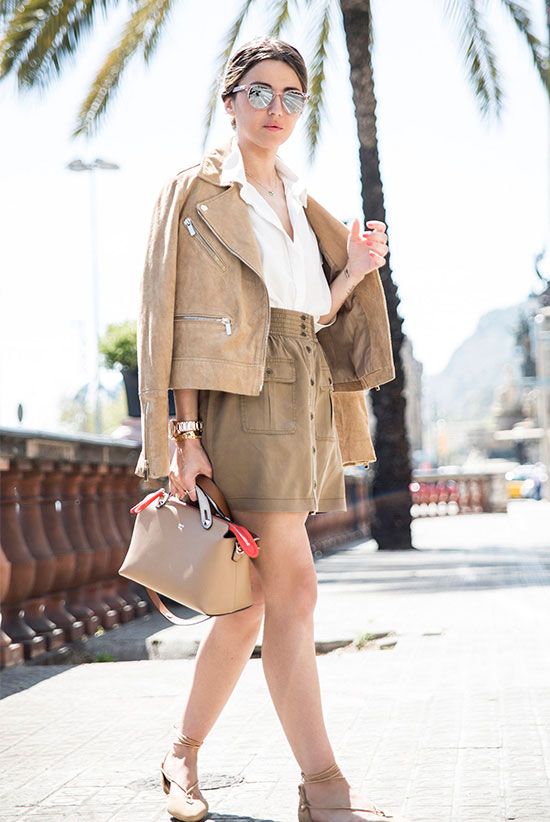 Street Style - The Top Blogger Looks Of The Week: Fashion Blogger 'Lovely Pepa' wearing a beige suede jacket, a white shirt, a beige paper bag mini skirt, nude suede lace-up flats, mirror sunglasses and a beige handbag. Spring outfit, summer outfit, comfy outfit, travel outfit, vacation outfit, beach outfit, neutral tone outfit, neutral outfit, casual outfit.