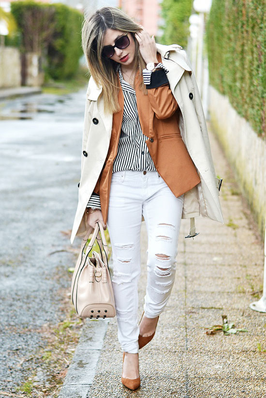 20 Ways To Style Your Favorite Trench Coat: Fashion Blogger 'Ma Petite by Ana' wearing a beige trench coat, a cognac blazer, a black stripe shirt, white distressed skinny jeans, brown heels, black sunglasses and a nude handbag. Trench coat outfit, fall outfit, winter outfit, layers outfit, casual outfit, night out outfit, street chic style.
