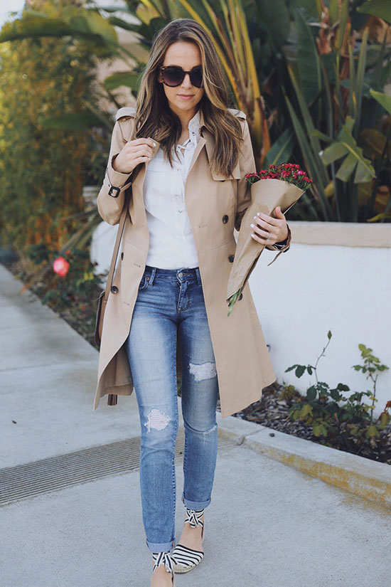 Street Style - The Top Blogger Looks Of The Week: Fashion blogger 'Merrick's Art' wearing a beige trench coat, a white lace-up blouse, distressed skinny jeans, black and white stripe espadrilles, brown sunglasses and a brown shoulder bag. Spring outfit, casual outfit, comfy outfit.