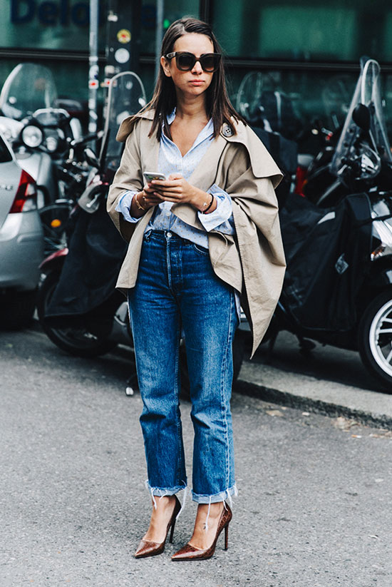 20 Ways To Style Your Favorite Trench Coat: Fashion It Girl Natasha Goldenberg wearing a beige trench cape, a light blue shirt, crop straight leg jeans, brown heels and brown sunglasses. Trench coat outfit, spring outfit, fall outfit, casual outfit, street chic style.