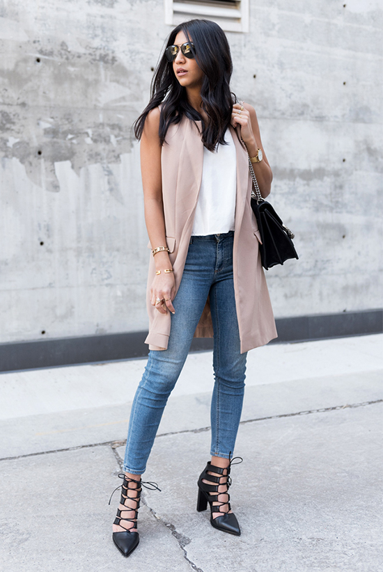 Street Style - The Top Blogger Looks Of The Week: Fashion blogger 'Not Your Standard' wearing a white tank top, a pale pink long vest, skinny jeans, black lace-up heels, aviator sunglasses and a black shoulder bag. Casual outfit, summer outfit, street chic style.