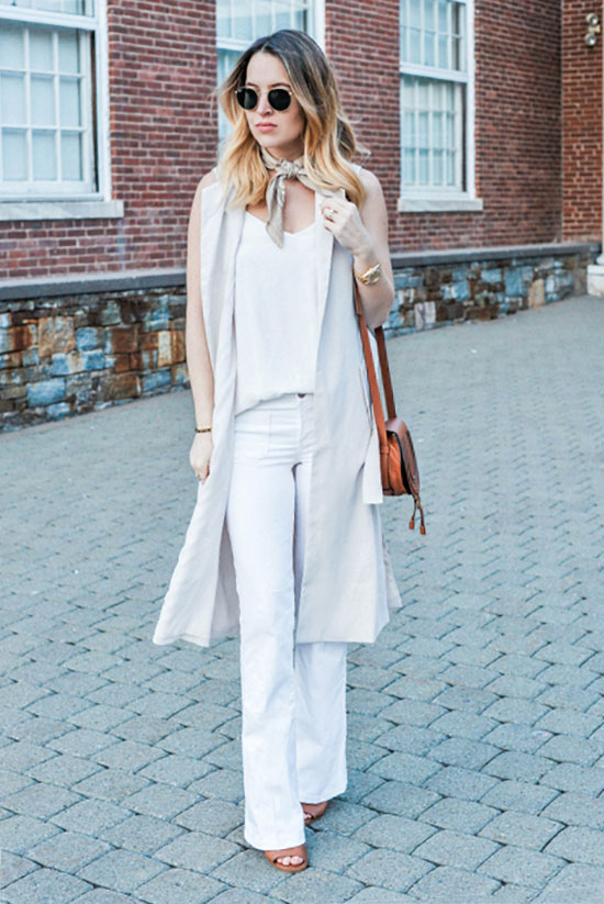 Street Style - The Top Blogger Looks Of The Week: Fashion Blogger 'Oh So Glam' wearing a beige long vest, a white cami top, white flare jeans, brown heeled sandals, a beige bandana, round aviator sunglasses and a brown shoulder bag. Summer outfit, casual outfit, 70s outfit, street chic style.