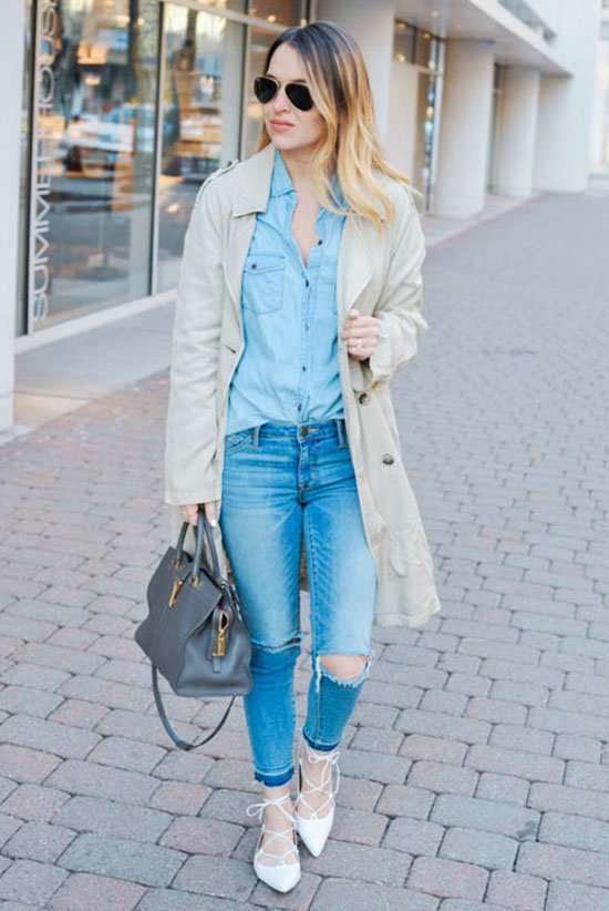 20 Ways To Style Your Favorite Trench Coat: Fashion Blogger 'Oh So Glam' wearing a beige trench coat, a chambray shirt, distressed skinny jeans, white lace-up flats, aviator sunglasses and a grey handbag. Trench coat outfit, spring outfit, fall outfit, comfy outfit, casual outfit, street style, street chic style, denim on denim outfit, double denim outfit.