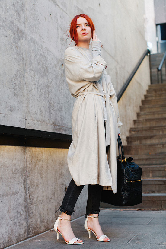 20 Ways To Style Your Favorite Trench Coat: Fashion Blogger 'Sea Of Shoes' wearing a beige trench coat, a white t-shirt, black washed skinny jeans, nude heeled sandals and a black handbag. Trench coat outfit, spring outfit, casual outfit, work outfit, street chic style.