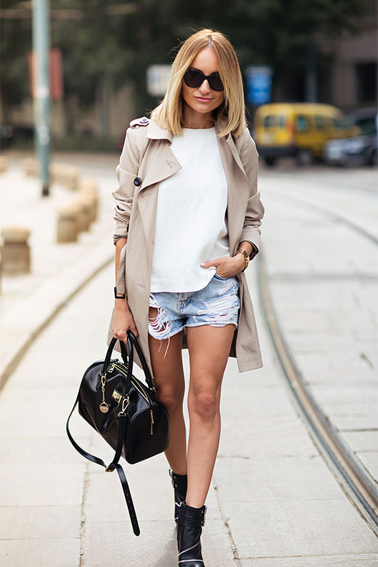 20 Ways To Style Your Favorite Trench Coat: Fashion It girl Sylvia wearing a beige trench coat, a white crew neck sweater, light distressed denim shorts, black booties, black sunglasses and a black handbag. Trench coat outfit, spring outfit, street style, street chic style, casual outfit.