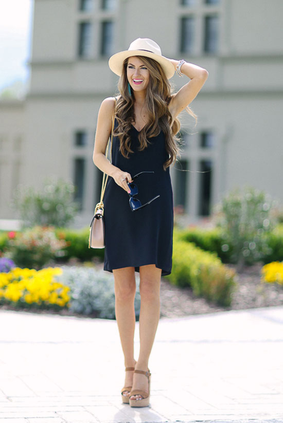 Street Style - The Top Blogger Looks Of The Week: Fashion Blogger 'Southern Curls & Pearls' wearing a straw hat, a black v-neck sleeveless dress, brown platform wedges and a blush shoulder bag. Summer outfit, travel outfit, vacation outfit, casual outfit, night out outfit, beach outfit.