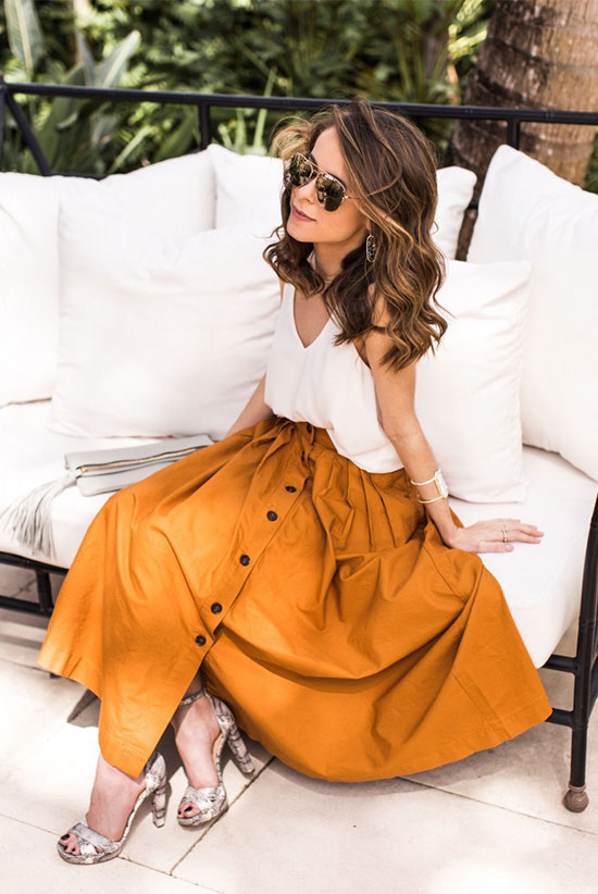 Street Style - The Top Blogger Looks Of The Week: Fashion Blogger 'The Style Bungalow' wearing a white cami top, a mustard button front midi skirt, grey snake print sandals and aviator sunglasses. Summer outfit, casual outfit, beach outfit, vacation outfit, street chic style.