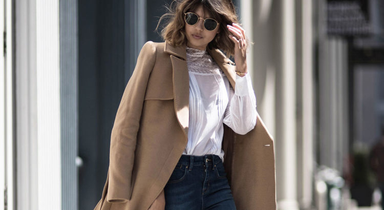 Street Style - The Top Blogger Looks Of The Week: Fashion Blogger 'Badlands' wearing a camel long coat, a white embroidered blouse, flare jeans, black booties and round aviator sunglasses. Fall outfit, spring outfit, casual outfit, comfy outfit.