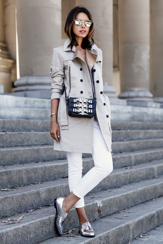 20 Ways To Style Your Favorite Trench Coat: Fashion Blogger 'Viva Luxury' wearing a beige trench coat, a grey t-shirt, white skinny jeans, silver oxfords, silver mirror sunglasses and a black buckle shoulder bag. Trench coat outfit, casual outfit, work outfit, tomboy outfit, comfy outfit, street style, street chic style, spring outfit, fall outfit.