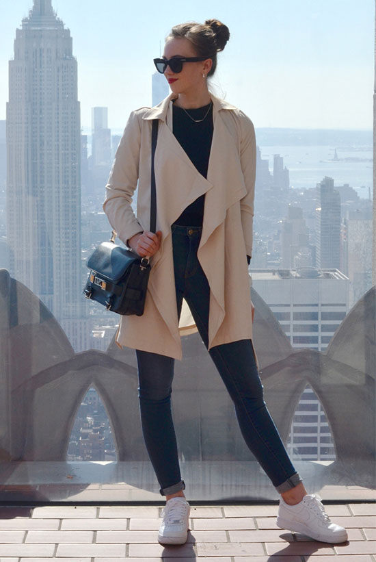 20 Ways To Style Your Favorite Trench Coat: Fashion Blogger 'Vogue Haus' wearing a beige trench coat, a black t-shirt, skinny jeans, white sneakers, black sunglasses and a black shoulder bag. Trench coat outfit, casual outfit, spring outfit, fall outfit, comfy outfit, sneakers outfit, street style, athleisure outfit.